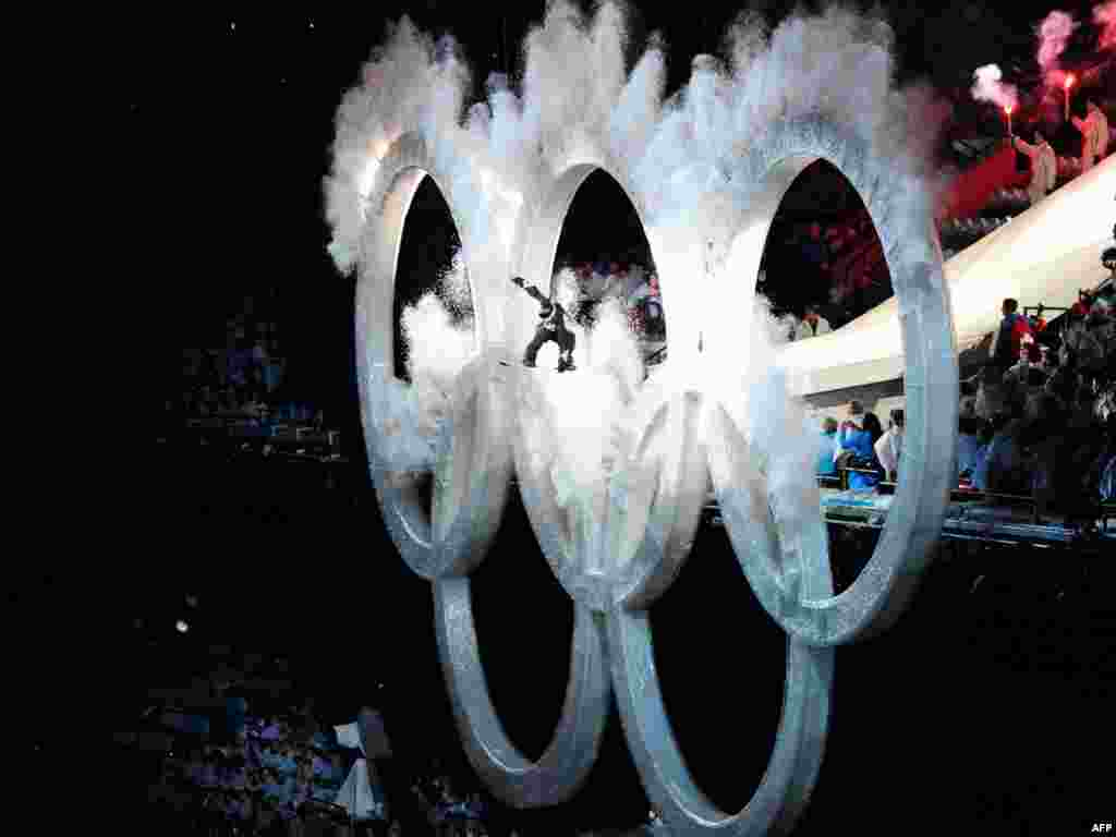 A snowboarder jumps through the Olympic rings during the opening ceremony of the Vancouver 2010 Winter Olympics. - Photo by Cris Bouroncle for AFP