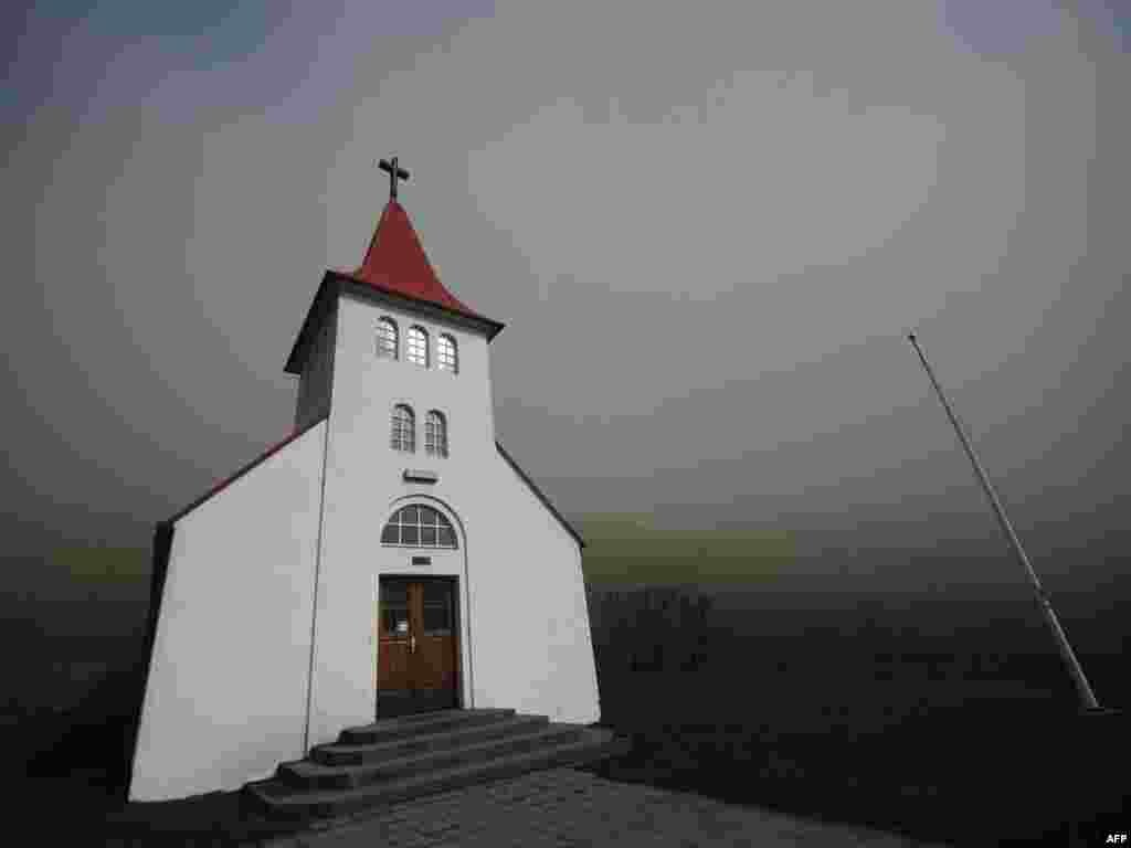 Smoke and ash from the Eyjafjallajokull volcano block daylight around a church near Asolfssakali. Photo by Emmanuel Dunand for AFP.