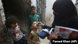 FILE: A Pakistani health worker gives a polio vaccination to a child in Karachi (November 2018).