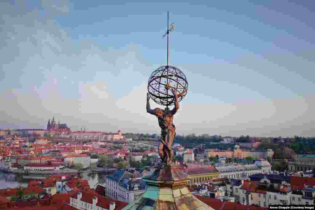 """Монумент на Атлас, който носи на раменете си """"небесната сфера"""" на върха на Клементиум, исторически комплекс от сгради, който включва метеорологична станция, която се използва от 1775 г. Статуята на Атлас е създадена от Матиас Бернард Браун (1684-1738), който е направил и някои от скулптурите на известния Карлов мост."""