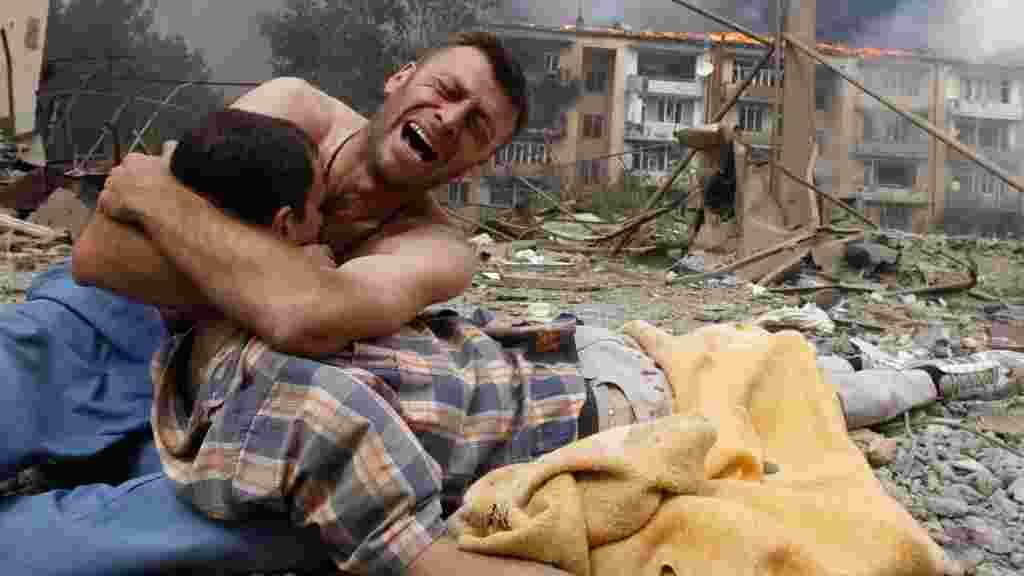 Грузин плачет, держа тело близкого человека, после российского бомбардировки 9 августа в Гори; Грузия, у административной границы с Южной Осетией