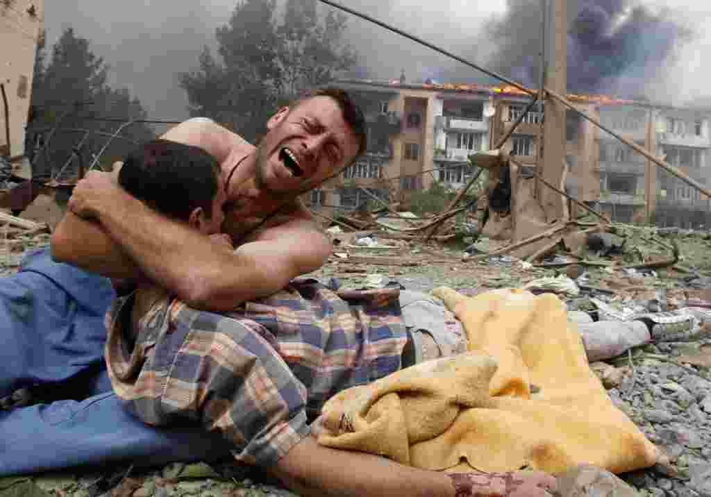 A Georgian man cries as he holds the body of a loved one after a Russian bombardment on August 9 in Gori, Georgia, near the border of the breakaway region of South Ossetia.