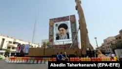"""Raketa """"Šahab-3"""", za koju se tvrdi da može nositi nuklearnu bojevu glavu, prikazana je pored portreta iranskog vrhovnog vođe ajatolaha Alija Hamneija u Teheranu 2019."""