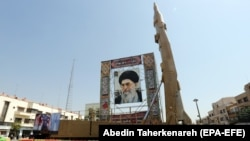 IRAN -- A Shahab-3 surface-to-surface missile is on display next to a portrait of Iranian Supreme Leader Ayatollah Ali Khamenei at a street exhibition by Iran's army and paramilitary Revolutionary Guard celebrating 'Defense Week' marking the 39th annivers