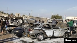 Residents gather at the site of a car-bomb attack in the Shuala district in Baghdad on January 22.