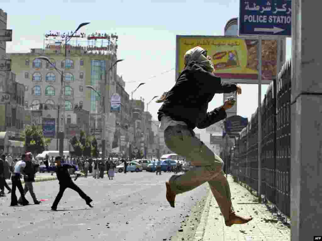 A Yemeni antigovernment protester jumps to throw stones toward a police station during clashes with regime loyalists in central Sanaa on February 17. At least 12 people were injured and police fired warning shots during the fierce clashes.Photo by Ahmad Gharabli for AFP
