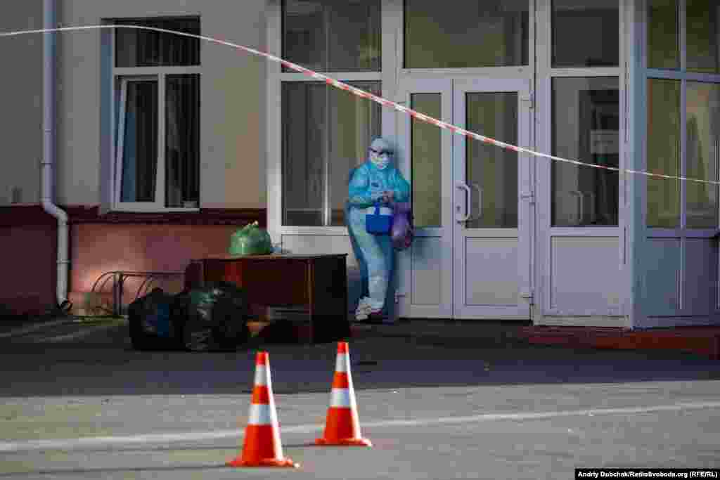 A medical worker collects supplies dropped off at Kalynivka's hospital. The facility is now effectively sealed off from the outside world. Waste is picked up and supplies are dropped off by people who avoid direct contact with the staff inside.