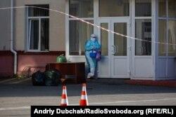 Медичний працівник у антивірусному захисному комбінезоні забирає ліки та передачі для хворих