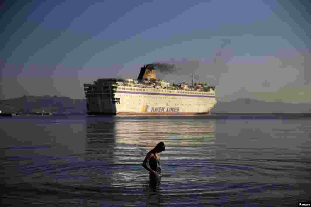 A migrant bathes as the passenger ship Eleftherios Venizelos leaves port on the Greek island of Kos. The ship -- carrying Syrian refugees -- was headed for the mainland as authorities struggle to cope with a wave of arrivals. The ship had acted as a floating accommodation and registration center and was heading for the northern port of Thessaloniki. (Reuters/Alkis Konstantinidis)