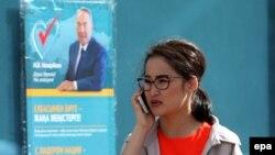 Девушка рядом с объявлением о дате проведения в Казахстане внеочередных выборов. Астана. 24 апреля 2015 года.