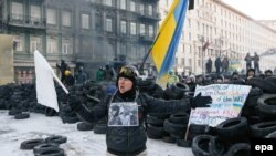 A protester shouts to riot police in front of a barricade during an antigovernment protest in downtown Kyiv.