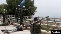Lebanese soldiers take positions as UN peacekeepers gesture toward Israeli soldiers at the Lebanese-Israeli border in Adaisseh village in August 2010.