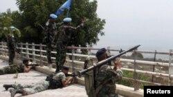 Lebanese soldiers take positions as UN peacekeepers gesture toward Israeli soldiers at the Lebanese-Israeli border in Adaisseh village in August 2010.