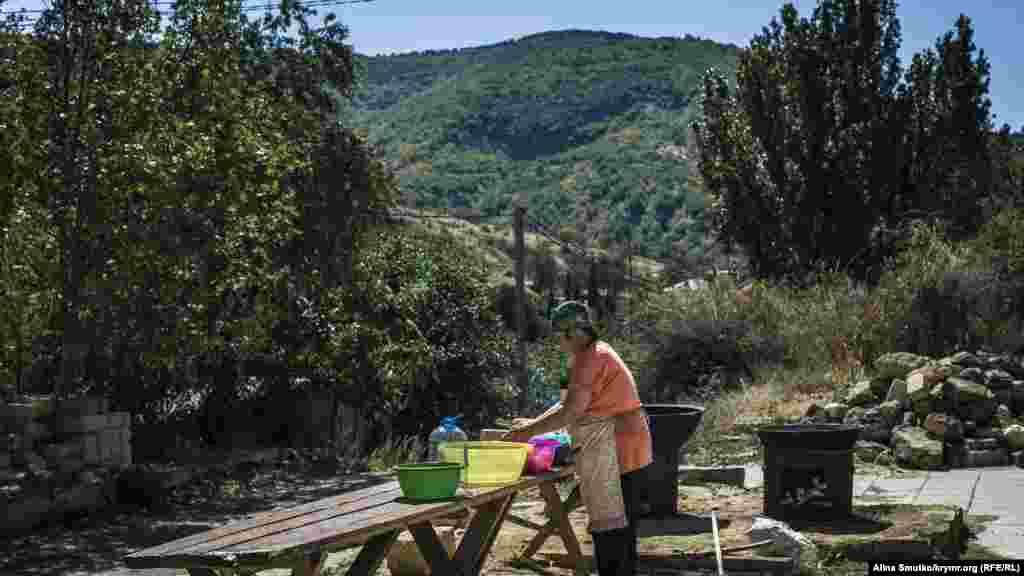 Женщина следит за приготовлением плова и шурпы
