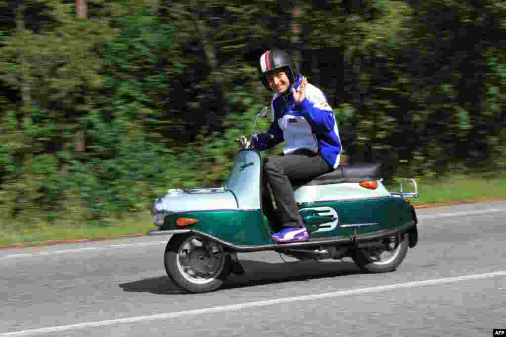 Czech Karel Abraham waves as he drives an old Cezeta scooter in Brno.The MotoGP world championships continue with the Czech Grand Prix in Brno on August 25. (AFP/Radek Mica)
