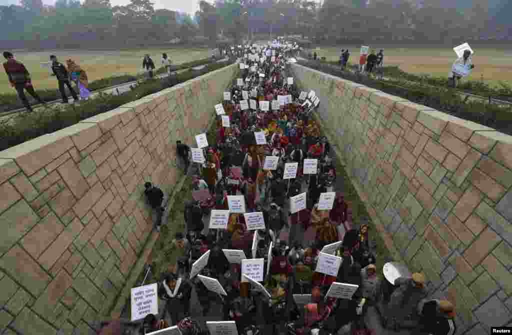 Women carrying placards attend a prayer ceremony in New Delhi for the victim of a gang rape. The ashes of the Indian student who died were scattered in the Ganges River as reports of more attacks stoked a growing national debate on violence against women. (Reuters/Adnan Abidi)
