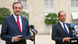 French President Francois Hollande (right) and Greek Prime Minister Antonis Samaras speaking to journalists in Paris on August 25.