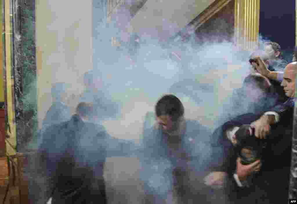 Members of the Kosovar parliament react after tear gas was launched by opposition lawmakers in the latest eruption of a long-running protest against agreements made with Serbia. (AFP/Driton Vitia)