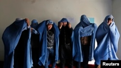 Male Afghan women's rights activists pose for media as they wear burqas to show their solidarity to Afghan women ahead of International Women's Day in Kabul on March 5.