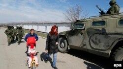 Әскерилер мінген көлік қасынан өтіп бара жатқан әйелдер. Симферополь, 14 наурыз 2014 жыл