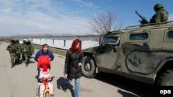 Fotografi e sotme në të cilin shihen këmbësoret duke kaluar afër një makine të blinduar të prodhimit rus në periferi të qytetit Simferopol në Krime të Ukrainës