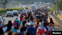Мигранты направляются в Австрию вдоль венгерской автомагистрали, 4 сентября 2015 года.