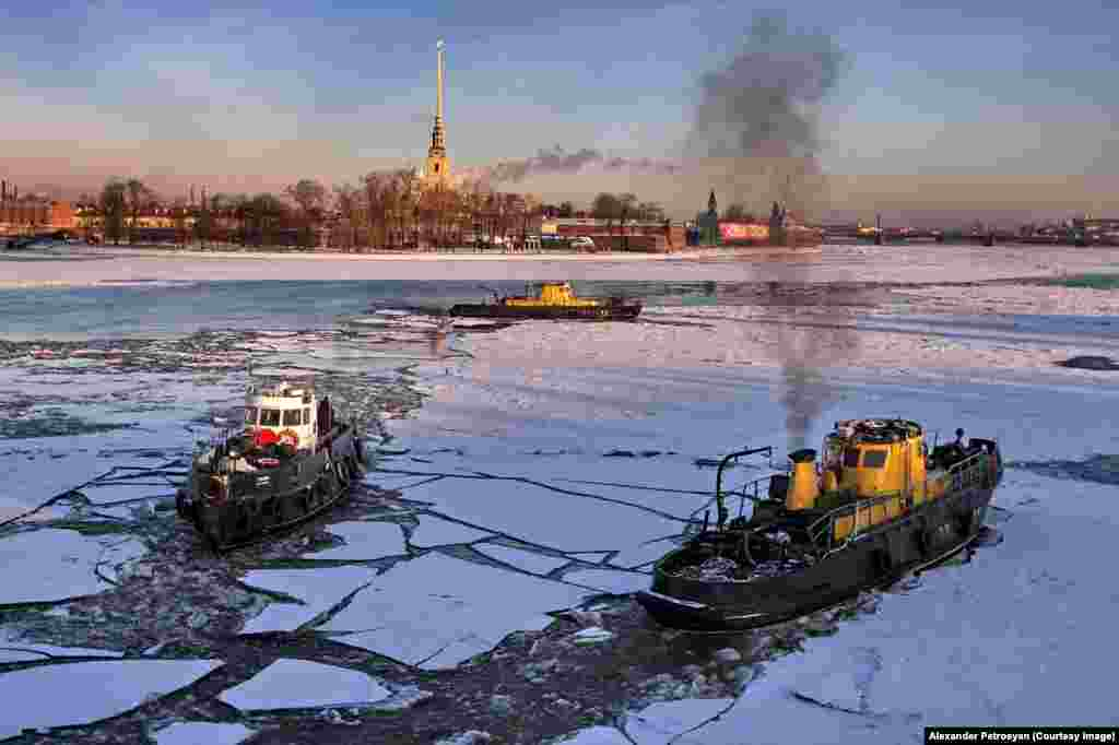 Boats cracking through ice on the River Neva.