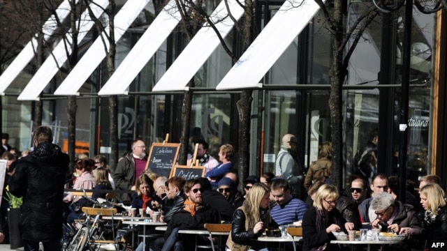 Swedes enjoy a sunny afternoon on the terrace of a bar in Stockholm.