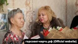 Глава горсовета Керчи Мая Хужина (л) вручает букет ветерану