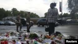 Британ жоокери өлтүрүлгөн жерге гүлчамбарлар коюлууда. 23-май, 2013-жыл.