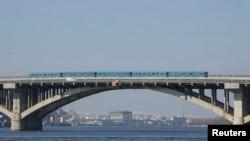 За даними ЗМІ, станції метро, розташовані поблизу мосту Метро в Києві зачинили через невідомого, який вийшов з автомобіля на мосту, зробив кілька пострілів у повітря і пригрозив підірвати міст