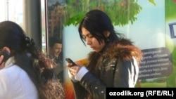 Uzbekistan - Uzbek girl is using a mobile phone, undated