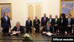 Премьер-министр Армении Тигран Саргсян (справа) и глава коллегии Евразийской экономической комиссии Виктор Христенко подписывают «Меморандум об углублении взаимодействия» между Арменией и ТС, Ереван, 6 ноября 2013 г.