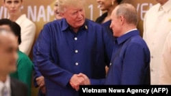U.S. President Donald Trump (left) shakes hands with Russia's President Vladimir Putin as they pose for a group photo ahead of the APEC summit leaders' dinner in Danang, Vietnam, on November 10.
