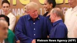 Президент США Дональд Трамп и президент России Владимир Путин (справа) во время обмена рукопожатиями. Дананг, 10 ноября 2017 года.