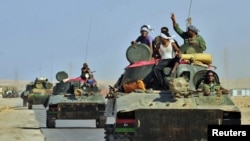 Libya -- Rebel tanks travel past Bin Jawad while on their way to Sirte, 29Aug2011