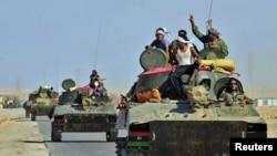 Libya -- Rebel tanks travel past Bin Jawad while on their way to Sirte, 29Aug2011