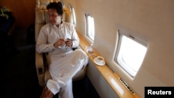 PAKISTAN -- Imran Khan, chairman of the Pakistan Tehreek-e-Insaf (PTI), political party, holds his tasbih, while having tea on a plane on his way to a campaign rally ahead of general elections in Sialkot, Pakistan July 12, 2018Reuters