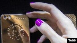 Алтын чапталып, ага Путиндин сүрөтү чегилген смартфон. Орусия