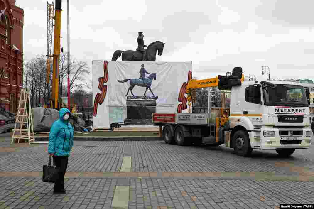 A masked woman looks over the scene on March 20. City authorities said the replica is only temporary and the original statue will be reinstalled by early May.