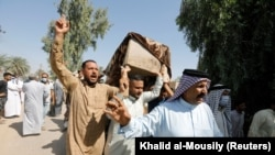 Mourners carry a coffin containing a victim of rocket attacks in the Abu Ghraib district on the outskirts of Baghdad on September 29.