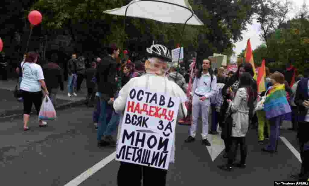 "In a reference to Putin's recent escapade flying an ultralight aircraft to try and teach young cranes how to migrate, this woman's sign reads: ""Abandon hope anyone flying behind me."""