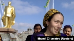 Türkmenistanyň ilkinji prezidenti S.Nyýazowyň altyn çaýylan heýkeliniň fonundaky altyn dişli zenan. Arhiw suraty