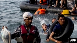 Migrants arrive on the shores of the Greek island of Lesbos after crossing the Aegean Sea from Turkey on a dinghy on September 9.