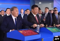 Chinese President Xi Jinping (right) and his Kazakh counterpart Nursultan Nazarbaev (left) turn on a symbolic lever during a ceremony in Astana on June 8, 2017, for a new container service.