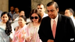 India's corporate giant Reliance Industries Ltd. Chairman Mukesh Ambani, right, accompanied by his wife Nita, second from left, arrives for the company's annual general meeting in Mumbai, India, Friday, June 3, 2011.