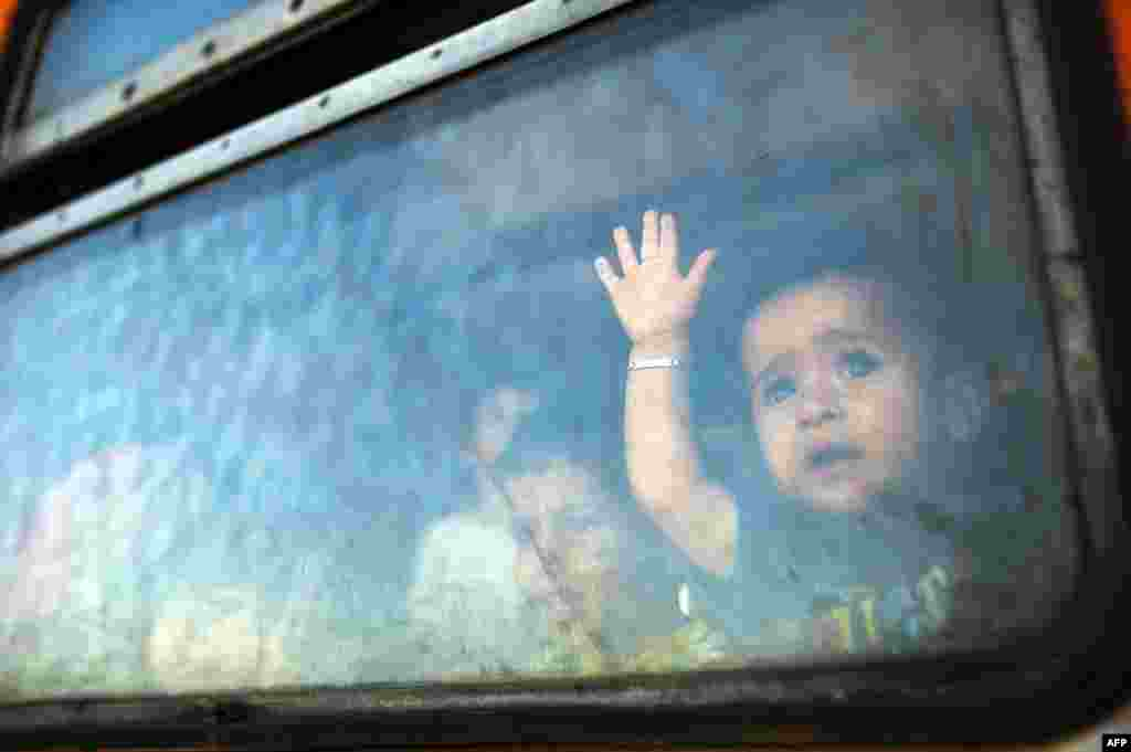 A migrant boy looks through a window onboard a train for Serbia at the new transit center for migrants at the border line between Greece and Macedonia near the town of Gevgelija, Macedonia. (AFP/Robert Atanasovski)