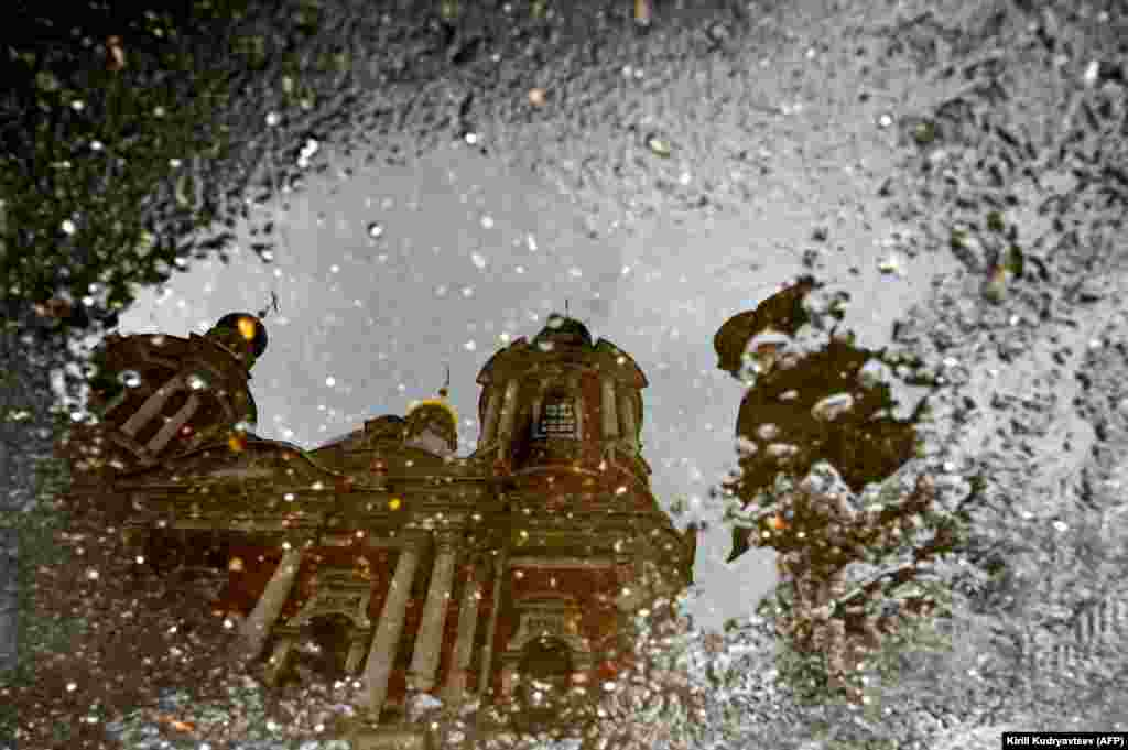 A man is reflected in a puddle as he walks past St. Clement's Church in Moscow. (AFP/Kirill Kudryavtsev)