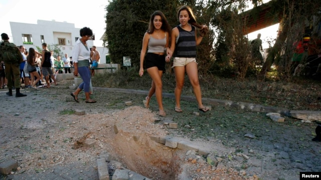 Onlookers walk past damage caused by a rocket fired from Lebanon into Israel near the northern city of Nahariya on August 22.