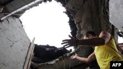 Житель Луганська дивиться в діру у стелі свого помешкання, 9 липня 2014 року